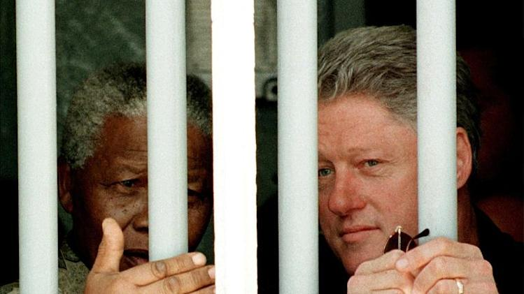 US President Bill Clinton (R) and South African President Nelson Mandela look out the jail cell window on March 27, 1998 where Mandela spent 18 of his 27 years as a political prisioner on Robben Island