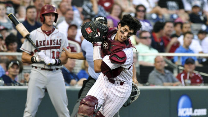 South Carolina catcher Dante Rosenberg scrambles to catch a foul ball hit by Arkansas' Jake Wise, who was out on the play, in the second inning of an NCAA College World Series baseball game in Omaha, Neb., Monday, June 18, 2012. On deck is Arkansas' Tim Carver (18). (AP Photo/Ted Kirk)