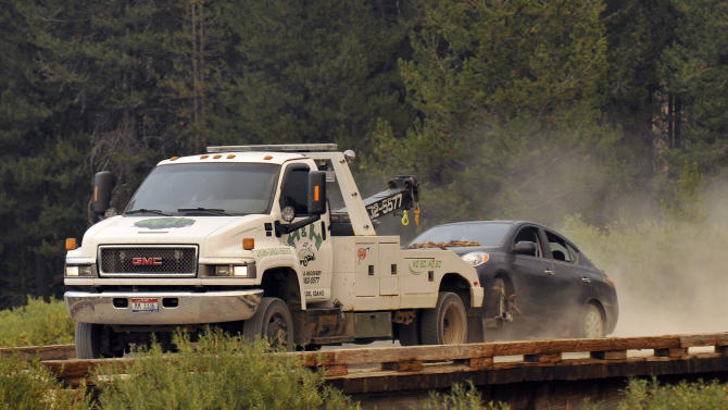 FILE- In this Aug. 10, 2013, file photo, James DiMaggio's car is towed to the town of Cascade after detectives finished searching it on a trail head bordering the Frank Church River of No Return Wilderness. The sister of James DiMaggio, who was killed in the Idaho wilderness after he was suspected of kidnapping a teen girl and killing her mother and brother in California, has filed a claim Thursday, July 30, 2015, seeking $20 million from the FBI. (AP Photo/Robby Milo, File)