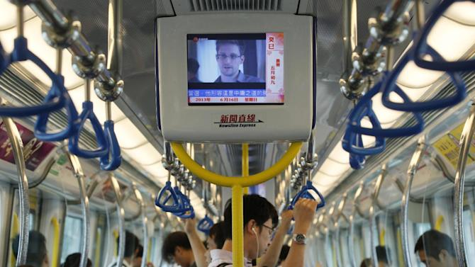 FILE - In this June 16, 2013 file photo a television screen shjows the news of Edward Snowden, a former CIA employee who leaked top-secret documents about sweeping U.S. surveillance programs, in the underground train in Hong Kong. Whisked out of a luxury Hong Kong hotel, vanishing into a mysterious wing of the Moscow airport, Edward Snowden's continent-jumping, hide-and-seek game seems like the stuff of a pulp thriller _ a desperate man's drama played out before a worldwide audience trying to decide if he's a hero or a villain. But the search for the former National Security Agency contractor who spilled government secrets has become something of a distracting sideshow, some say, overshadowing at least for now the important debate over the government's power to seize the phone and Internet records of millions of Americans to help wage the war on terrorism. (AP Photo/Kin Cheung, File)