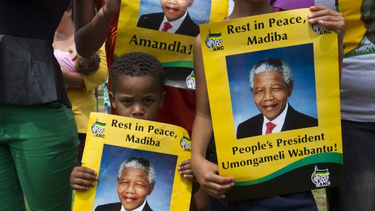 A boy holds a poster with an image of former South African President Nelson Mandela near Qunu