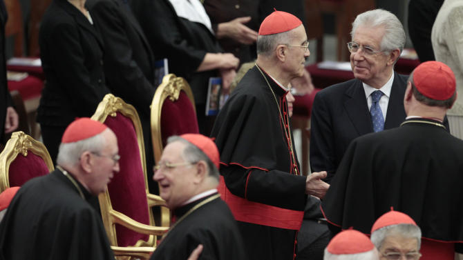 Italian Premier Mario Monti, right, talks to Vatican Secretary of State Tarcisio Bertone, second from right, as they wait for the start of a concert offered by Italian President Giorgio Napolitano to Pope Benedict XVI at the Vatican, Friday, May 11, 2012. (AP Photo/Gregorio Borgia)