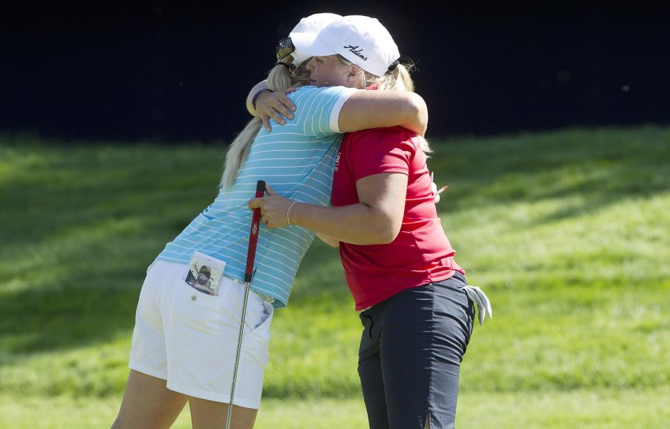 Brittany Lincicome, left, hugs Caroline Hedwall, of Sweden, after they finished the third round of the Canadian Women's Open golf tournament in Edmonton, Alberta, Saturday, Aug. 24, 2013. (AP Photo/The Canadian Press, Jason Franson)