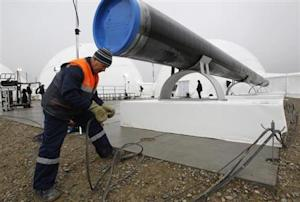 A worker checks wires in front a gas pipe before the…