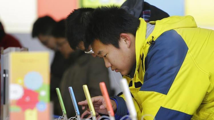A customer tests an iPhone 5C at an Apple store in Beijing