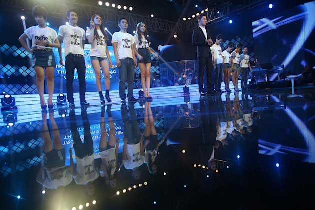 "In this photo taken Friday, Oct. 12, 2012, contestants, wearing T-shirts with a slogan ""Listen responsibly"" for a campaign against online piracy, stand on stage at a ""Vietnam Idol 2012"" in Ho Chi Minh City, Vietnam. The campaign is aimed at Zing.vn and other copyright violated websites. Zing.vn, one of globe's top 550 most visited websites, is a wildly popular website laden with unlicensed songs and Hollywood movies, a prime exhibit of the digital piracy that is strangling the music industry in Asia and eroding legitimate online sales around the world. (AP Photo/Na Son Nguyen)"
