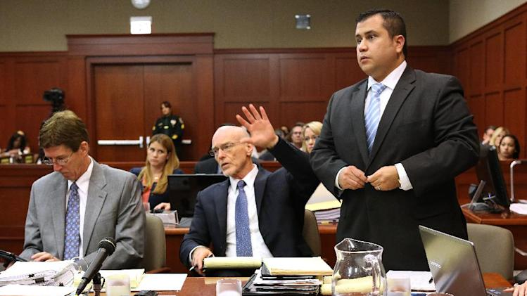George Zimmerman, with his attorneys, Mark O'Mara, left, and Don West, center, stands to be identified by state witness Chris Serino, a Sanford police officer, during his testimony in his trial in Seminole circuit court, in Sanford, Fla., Monday, July 1, 2013. West is signaling to the witness that his client will stand to be identified. Zimmerman has been charged with second-degree murder for the 2012 shooting death of Trayvon Martin. (AP Photo/Orlando Sentinel, Joe Burbank, Pool)