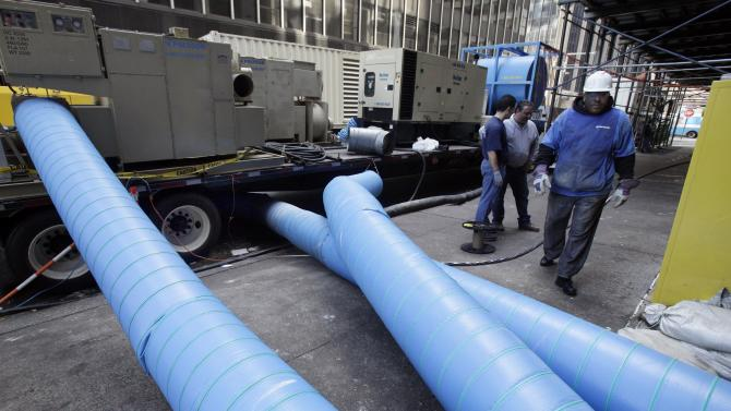 Giant drying blowers snake into a building in New York's Financial District, Monday, Nov. 12, 2012. Two weeks after Sandy hit, more than 75,000 people remained without power Monday in the most densely populated area of the United States.  (AP Photo/Richard Drew)