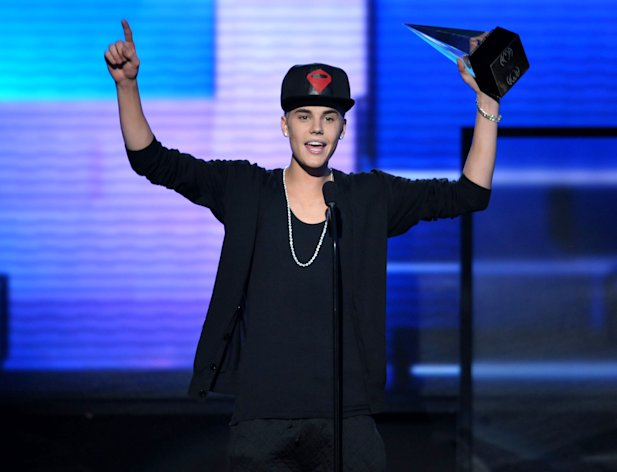 "FILE - In this Nov. 18, 2012 file photo, Justin Bieber accepts the award for favorite album - pop/rock for ""Believe"" at the 40th Anniversary American Music Awards, in Los Angeles. The Los Angeles City Attorney's Office appealed on Wednesday Dec. 12, 2012, a criminal court judge's ruling tossing anti-paparazzi counts against a photographer charged with driving recklessly in pursuit of Bieber. (Photo by John Shearer/Invision/AP, File)"