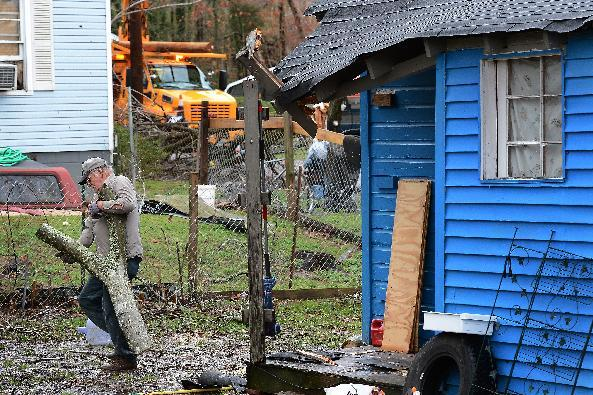 Thomas Ivey carries section of a tree he cut up after it was blown over by tornado that hit the corner of his friend's house     Wednesday, Jan. 30, 2013, in Ashland City, Tenn. Around 25 homes in Ashland City had minor damage. (AP Photo/Mark Zaleski)