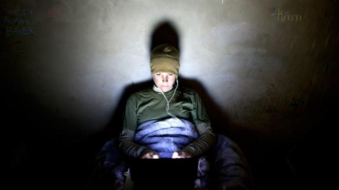 A U.S. Marine works late into the night on her computer at a base in Afghanistan.