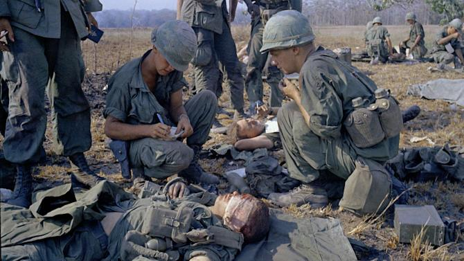 FILE - In this April 2, 1967 file photo shot by Associated Press photographer Horst Faas, wounded U.S. soldiers are treated on a battle field in Vietnam. Faas, a prize-winning combat photographer who carved out new standards for covering war with a camera and became one of the world's legendary photojournalists in nearly half a century with The Associated Press, Thursday May 10, 2012. He was 79. (AP Photo/Horst Faas)