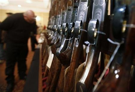 A man looks at a shotgun during the East Coast Fine Arms Show in Stamford, Connecticut, January 5, 2013. REUTERS/Carlo Allegri