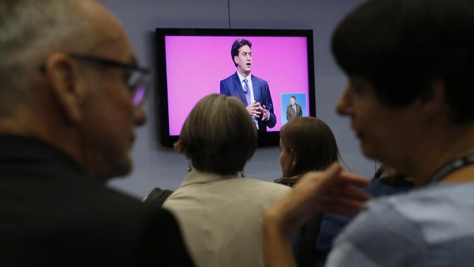 Delegates watch Britain's opposition Labour Party leader Miliband on a screen during the Labour party's annual conference in Manchester, northern England