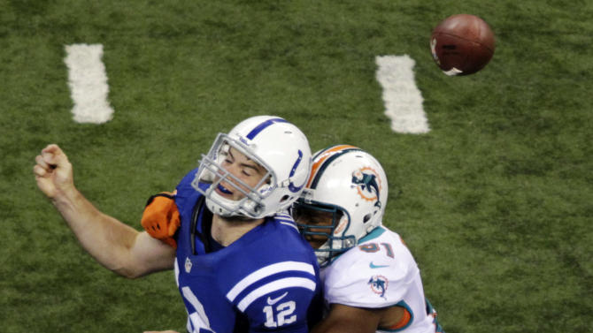 Indianapolis Colts quarterback Andrew Luck, left, fumbles the ball as he is hit by Miami Dolphins defensive end Cameron Wake during the second half of an NFL football game in Indianapolis, Sunday, Nov. 4, 2012. The Colts recovered the ball. (AP Photo/AJ Mast)