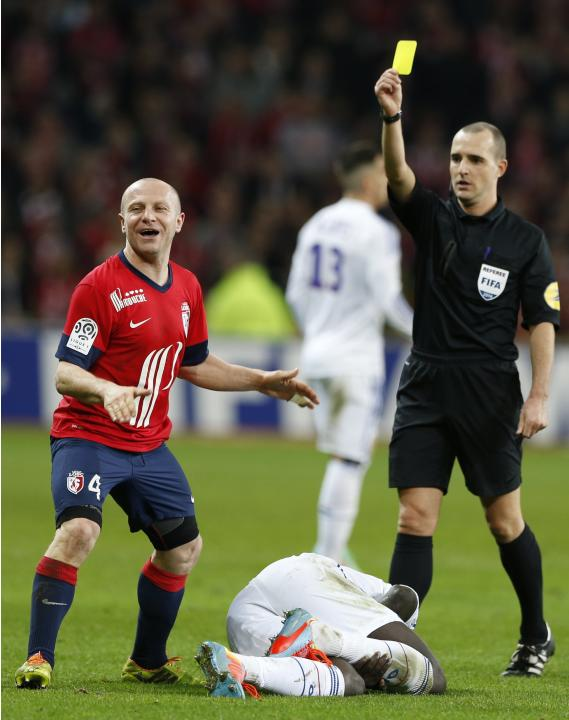 Lille' Balmont receives a yellow card during their French Ligue 1 soccer match against Lyon in Villeneuve d'Ascq
