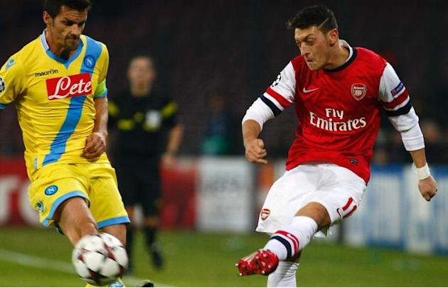 Arsenal's Mesut Ozil fights for the ball with Napoli's midfielder Christian Maggio during the UEFA Champion's League group F football match between SSC Napoli and Arsenal FC at the San Pao