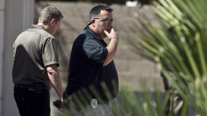 An investigator walks in front of the house, where police say a man shot and killed four people, including a toddler, before killing himself, in Gilbert, Ariz., on Wednesday, May 2, 2012. Police say the man was armed with several firearms, and officers recovered two handguns and a shotgun. (AP Photo/The Arizona Republic, Pat Shannahan)