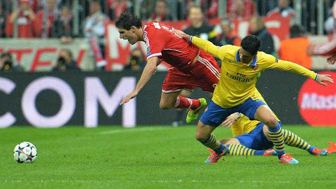 Bayern's Javier Martinez of Spain, left, and Arsenal's Mikel Arteta challenge for the ball during the Champions League round of the last 16 second leg soccer match between FC Bayern Munich and Arsenal FC in Munich, Germany, on Tuesday, March 11. 2014