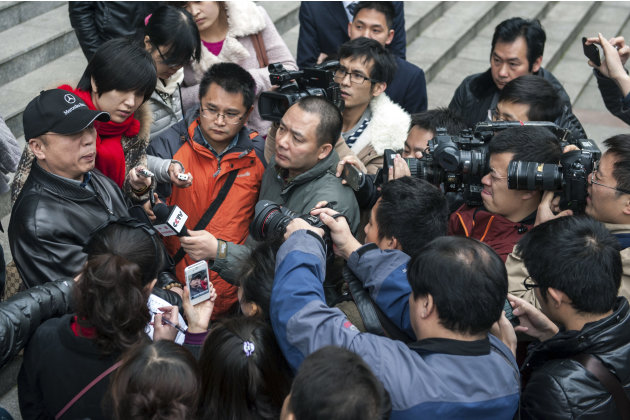 In this photo taken Thursday, Nov. 29, 2012, Li Zhuang, an ex-lawyer who claims he was framed and wrongfully jailed for 18 months, is surrounded by journalists in front of  the Chongqing No. 1 Interme