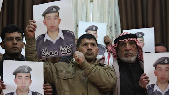 Relatives of Islamic State captive Jordanian pilot al-Kasaesbeh hold his poster as they take part in a rally in his support at the family's headquarters in the city of Karak