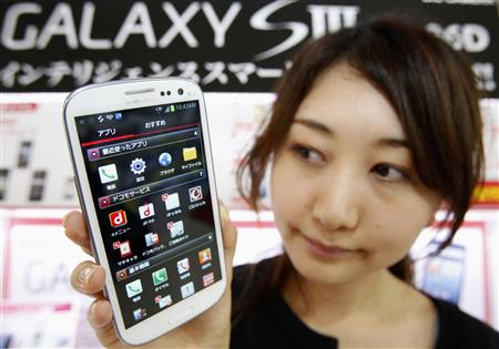 File photo of an employee of NTT Docomo Inc holding a Samsung Galaxy S III smartphone during a launch event in Tokyo