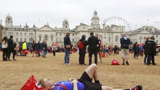 A runner rests on the gravel of  Horse Guards Parade after finishing the London Marathon