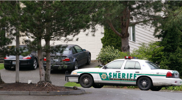 A sheriff's car is parked in a woodsy suburban area adjacent to a wilderness area and nearby trail access several miles from where a gun-toting survivalist is suspected of killing his wife and daughte