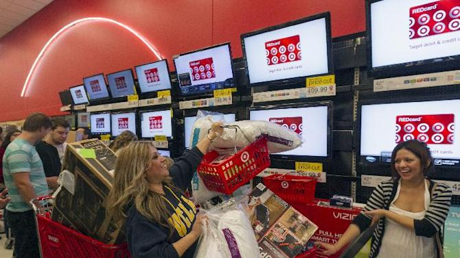 FILE - In this Nov. 22, 2012 file photo, Shopper Roxanna Garcia, middle, waits in line to pay for her over a $1000.00 gifts at the Target store in Burbank, Calif. Now that the U.S. has averted a default on its debt that could have sent the economy into a tailspin, it seems retailers avoided a train wreck heading into the holiday shopping season. Retailers hope that shoppers forget about the fact that the plan offers only a short reprieve until early next year long enough to open their pocketbooks. But they're fearful that consumers, facing a bombardment of news about continued political bickering, could hunker down until there's a permanent resolution. (AP Photo/Damian Dovarganes)