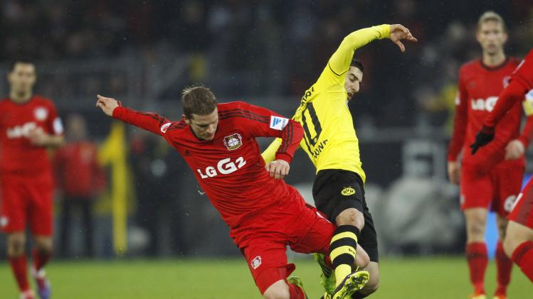 Borussia Dortmund's Mkhitaryan tackles Bayer Leverkusen's Bender during the German first division Bundesliga match in Dortmund