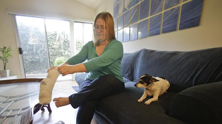"In this Tuesday, Jan. 29, 2013 photo, Meliisa Duffy prepares to leave for work as her dog, a pure bred rat terrier named Dinky, anxiously watches her put on her socks and shoes in Carlsbad, Calif.  ""She starts to get anxious when I am getting ready to go out, whining, pacing, shivering,"" Duffy says. Being left with a food-dispensing toy calms her reaction to Duffy's departure and has longer-lasting effects as well.  (AP Photo/Lenny Ignelzi)"