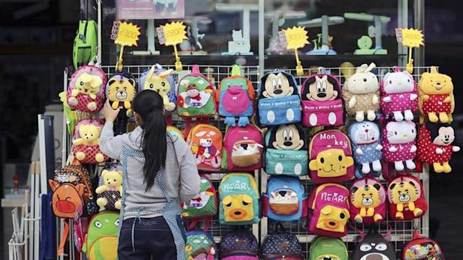A vendor arranges school bags at her stall in Kunming, Yunnan province, October 17, 2013. REUTERS/Wong Campion