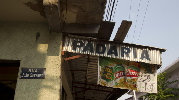 In this Dec. 28, 2012 photo, a sign marks a street name near a bakery in the Mare shantytown in Rio de Janeiro, Brazil. The city's densest neighborhoods, its favelas, or shantytowns blanket entire hillsides, providing most of the city's affordable housing. Now, those communities are being charted after decades of informality, each route and alley outlined and their names researched. Being left off the map had meant whole communities were unable to receive mail at home. It had also blocked people from giving required information on job applications, getting a bank account or telling the police or fire department where to go in an emergency call. (AP Photo/Silvia Izquierdo)