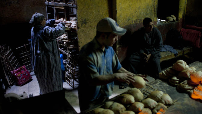 FILE - In this Thursday, Dec. 1, 2011 file photo, Egyptians work at a bakery in the al-Azhar quarter in Cairo, Egypt. Increasingly unaffordable subsidy programs pose a growing challenge across the Middle East and North Africa, with governments caught between demands by international lenders to scale back economically toxic handouts and fears of a popular backlash. (AP Photo/Bernat Armangue, File)