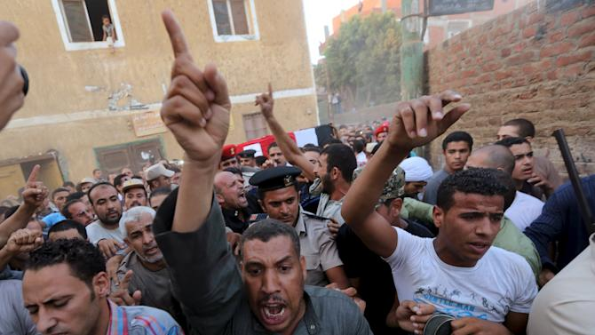 Relatives of 21-year-old Mohamed Adel, one of the army officers who died in yesterday's Sinai attacks, carry his coffin during his funeral in Al-Kaliobeya, near Cairo, Egypt