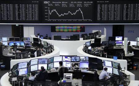 Traders work at their desks in front of DAX board at Frankfurt stock exchange