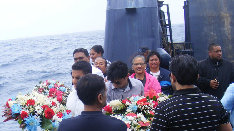 Two members of the Suleman family prepare to lay the wreaths during a memorial service honoring the U.S. teenager who died and his father who is missing after their plane crashed during an attempt to circumnavigate the world, Sunday, July 27, 2014, where nearly a hundred people gathered on a ferry off the coast of American Samoa. The body of 17-year-old Haris Suleman was found shortly after his plane crashed in the Pacific Ocean on Tuesday after leaving Pago Pago. U.S. Coast Guard officials on Sunday said they were suspending the search for 58-year-old Babar Suleman. (AP Photo/Fili Sagapolutele)