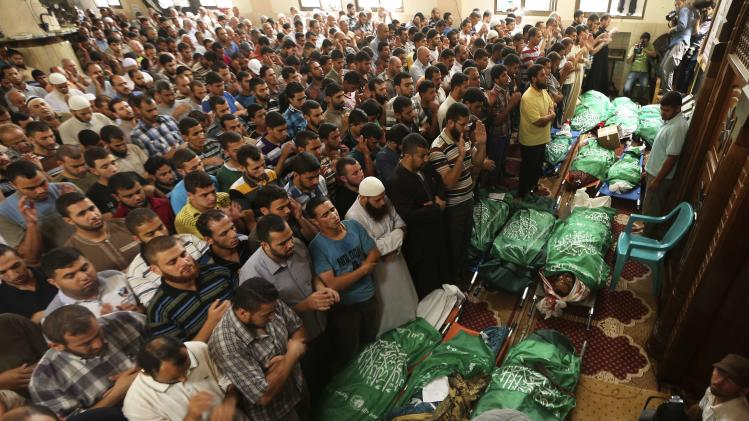 People pray near the bodies of members of Al-Batsh's family during their funeral at a mosque in Gaza City