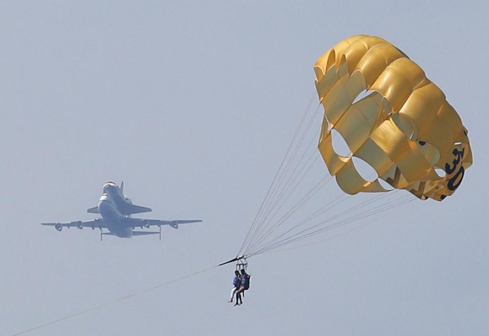 Space Shuttle Endeavour, mounted on NASA's Shuttle Carrier Aircraft (SCA), flies near parasailers in Santa Monica, Calif., Friday, Sept. 21, 2012. (AP Photo/Jae C. Hong)