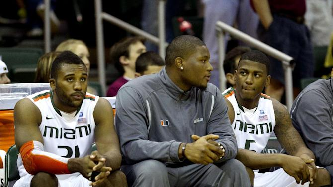 Miami basketball player Reggie Johnson, center, sits on the bench talking to teammates DeQuan Jones, right, and Erik Swoope during the first half of an NCAA college basketball game against Florida State in Coral Gables, Fla., Sunday, Feb. 26, 2012. Miami ruled Johnson ineligible to play. (AP Photo/J Pat Carter)