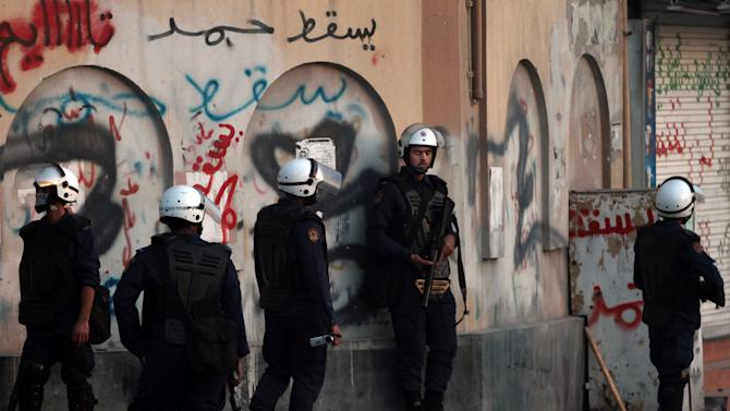 """Riot police watch for Bahraini anti-government protesters during clashes in Ma'ameer, Bahrain, Thursday, Jan. 24, 2013. Riot police in Bahrain fired tear gas and stun grenades at anti-government protesters whose chants included calls to reject proposed talks aimed at easing nearly two years of unrest in the Gulf nation. Graffiti on the wall repeatedly reads, """"down with Hamad,"""" referring to the king of Bahrain. (AP Photo/Hasan Jamali)"""