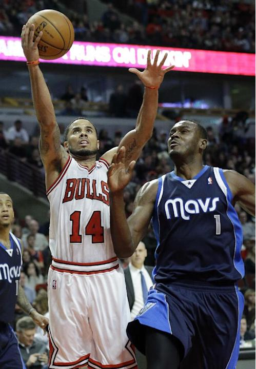 Chicago Bulls guard D.J. Augustin (14) drives to the basket against Dallas Mavericks center Samuel Dalembert (1) during the second half of an NBA basketball game in Chicago on Saturday, Dec. 28, 2013.