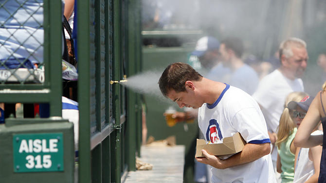 Chicago Cub sfan Ross Perry of Waukesha, Wis., cools off during 95-degree heat under the mist maker in the right field bleachers before Chicago Cubs played the Florida Marlins in a baseball game Sunday July 17, 2011, in Chicago. (AP Photo/Charles Cherney)