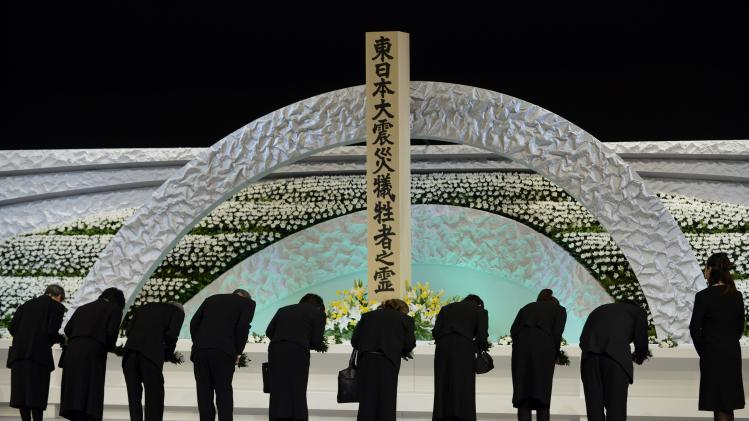 Relatives of victims of the March 11, 2011 earthquake and tsunami bow to the altar as they offer chrysanthemums for the victims at the national memorial service in Tokyo