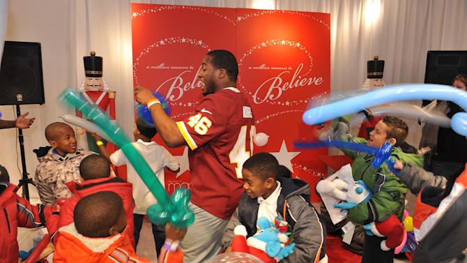 """IMAGE DISTRIBUTED FOR MACY'S - In this image released on Wednesday, Dec. 12, 2012, Alfred Morris entertains children with their balloon swords at the Macy's """"Covered for the Holidays"""" event in Washington, DC. Macy's and the Washington Redskins hosted the annual """"Covered for the Holidays"""" event at Metro Center for 300 local underserved children. (Larry French/AP Images for Macy's)"""