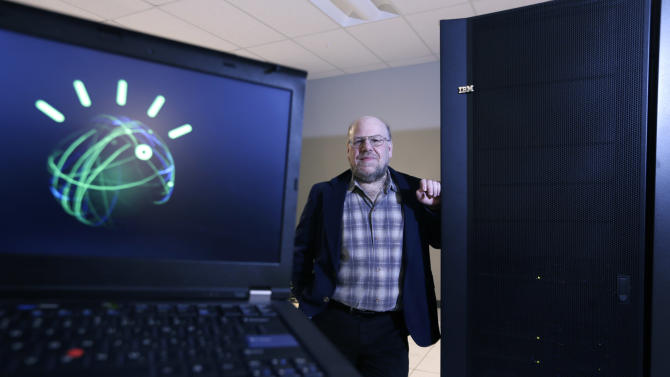 "Jim Hendler, who heads the computer science department at Rensselaer Polytechnic Institute, poses next to the the supercomputer Watson at the Computational Center for Nanotechnology Innovations on Tuesday, Jan. 29, 2013, in Troy, N.Y. Watson, the question-answering supercomputer best known for beating human champions on ""Jeopardy!,"" is going to college. IBM is announcing Wednesday that it will provide a Watson system to RPI, the first time a version of the computer is being sent to a university. The avatar on the computer screen at left represented Watson on ""Jeopardy!."" (AP Photo/Mike Groll)"
