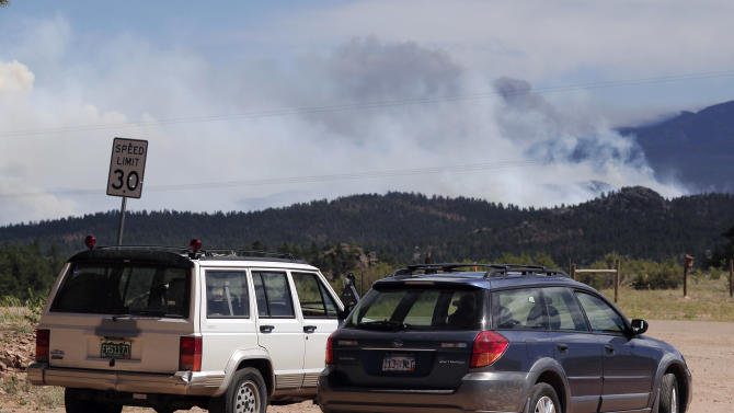 Residents of nearby subdivisions sit in their vehicles and look on as heavy smoke billows off the ridges east of Red Feather Lakes, Colo., on Sunday, June 17, 2012, as a stubborn wildfire continues to burn in northern Colorado. Strong winds are fanning the blaze that has destroyed at least 181 homes, the most in the state's history. (AP Photo/David Zalubowski)