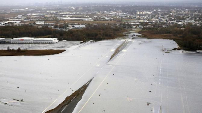 A runway at the Teterboro Airport is flooded in the wake of superstorm Sandy on Tuesday, Oct. 30, 2012, in NewJersey. Travel in the Northeast creaked back into motion on Wednesday, Oct. 31, 2012, at a grinding, patchy recovery that made it clear that stranded travelers will struggle to get around for days to come. (AP Photo/Mike Groll)
