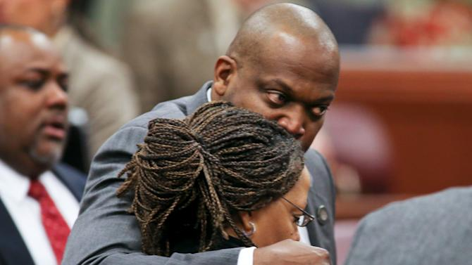 CORRECTS DATE Nevada Assembly Majority Leader William Horne, D-Las Vegas, hugs Assemblywoman Dina Neal, D-North Las Vegas, following an emotional and historic vote to expel fellow Assemblyman Steven Brooks, D-North Las Vegas, during the Assembly floor session at the Legislative Building in Carson City, Nev., on Thursday, March 28, 2013. Neal was the lone dissenting vote when a bipartisan select committee empanelled to look into the North Las Vegas Democrat's behavior voted 6-1 Tuesday to recommend expulsion. (AP Photo/Cathleen Allison)