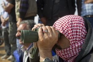 A man who says he's a refugee from Kobani watches…